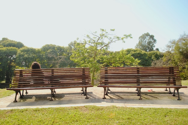 Frau, die auf einer bank in einem naturpark sitzt.