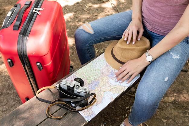 Frau, die auf einer bank mit reisendem zubehör sitzt