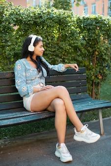 Frau, die auf einer bank sitzt und musik hört Kostenlose Fotos