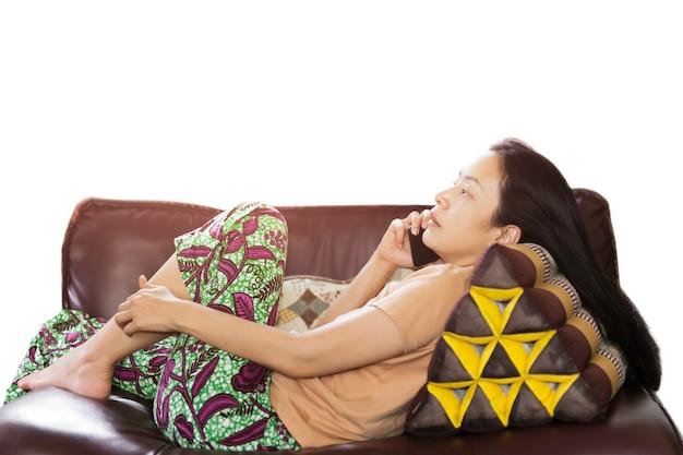 Frau, die auf einer couch liegt und am smartphone spricht, isoliert im beschneidungspfad.