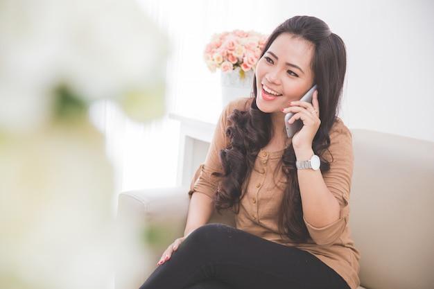 Frau, die auf einer couch sitzt und freund mit smartphone anruft