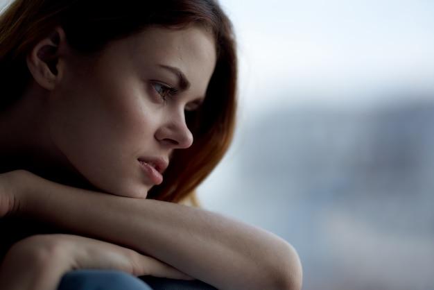 Frau, die auf einer fensterbank sitzt, die mit einer nachdenklichen ansicht der deckenruhe bedeckt ist