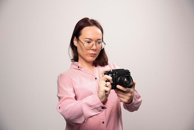 Frau, die auf einer kamera auf einem weiß schaut. foto in hoher qualität