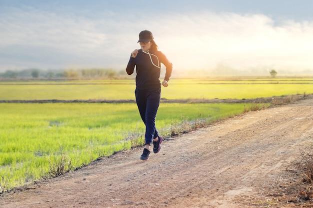 Frau, die auf einer landstraße während des sonnenuntergangs des grünen naturhintergrundes läuft