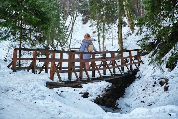Frau, die auf einer langen hölzernen brückenfußgängerbrücke in der schneebedeckten bergschlucht im winter geht