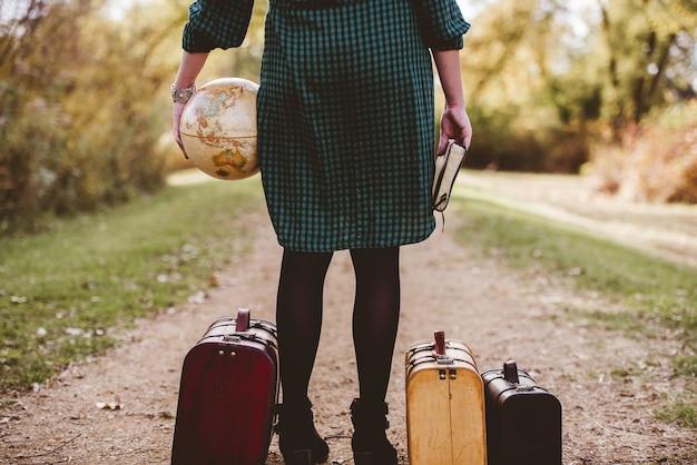 Frau, die auf einer leeren straße nahe ihrem alten koffer steht, während sie die bibel und eine schreibtischkugel hält