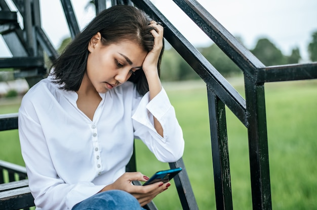 Frau, die auf einer leiter betrachtet ein intelligentes telefon und hat druck sitzt