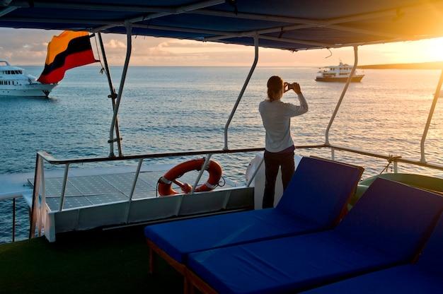 Frau, die auf einer lieferung steht und, punta suarez, espanola-insel, galapagos-inseln, ecuador fotografiert