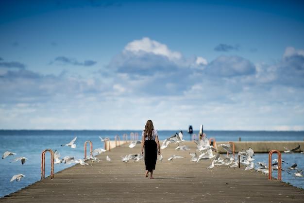 Frau, die auf einer promenade steht, die von vögeln umgeben ist
