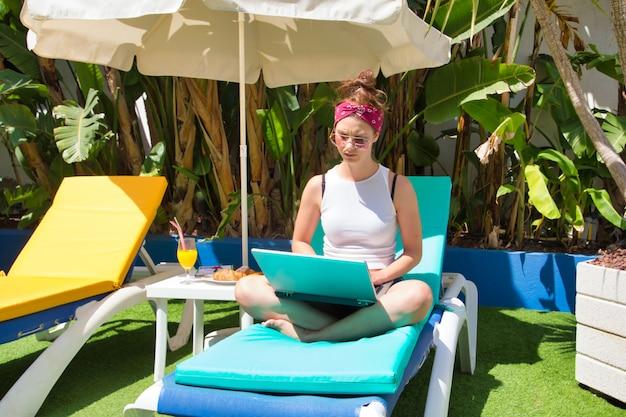 Frau, die auf einer sonnenliege unter einem regenschirm sitzt, während sie mit einem laptop arbeitet