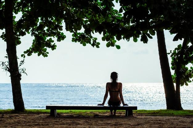 Frau, die auf einer strandbank entspannt. sommerferienkonzept