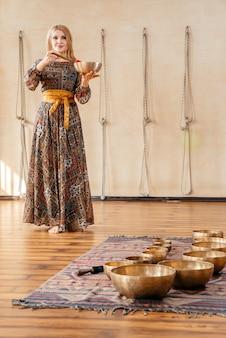 Frau, die auf einer tibetischen singenden schüssel für klangtherapie spielt