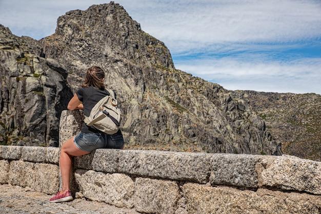 Frau, die auf einer wand mit einem rucksack sitzt, der die serra da estrela in portugal betrachtet
