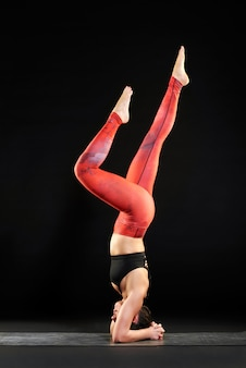 Frau, die auf einer yogamatte tut einen kopfstand ausarbeitet