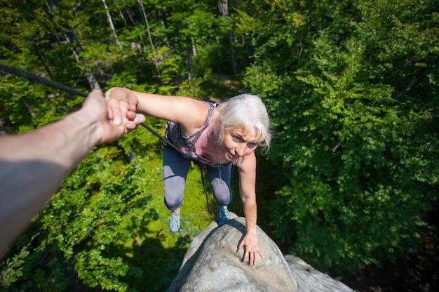Frau, die auf felsen, ihr partner steigt, der ihre helfende hand gibt