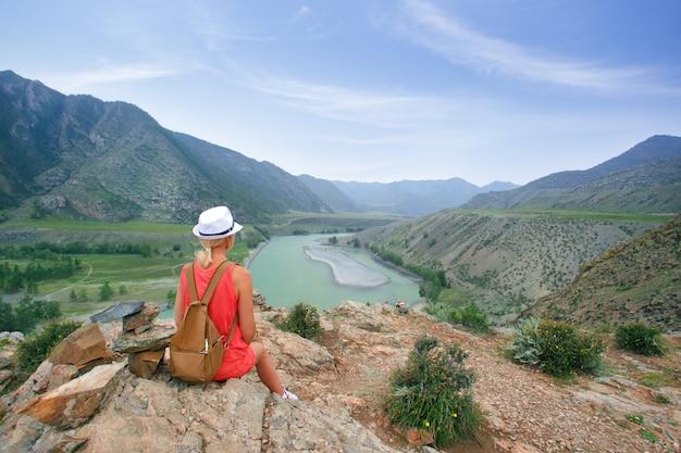 Frau, die auf felsigem stein sitzt und berge im sommer betrachtet.