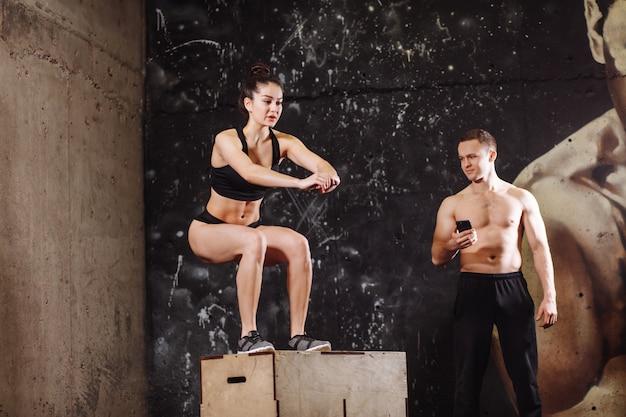 Frau, die auf fit box mit männlichem trainer springt