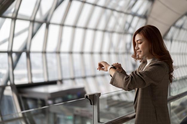 Frau, die auf flug wartet und intelligente uhr im flughafen schaut