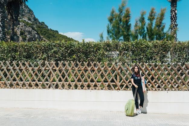 Frau, die auf gartenzaun mit dem halten der reisenden koffertasche am freien sich lehnt