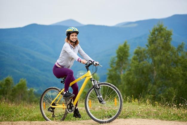Frau, die auf gelbem fahrrad reitet
