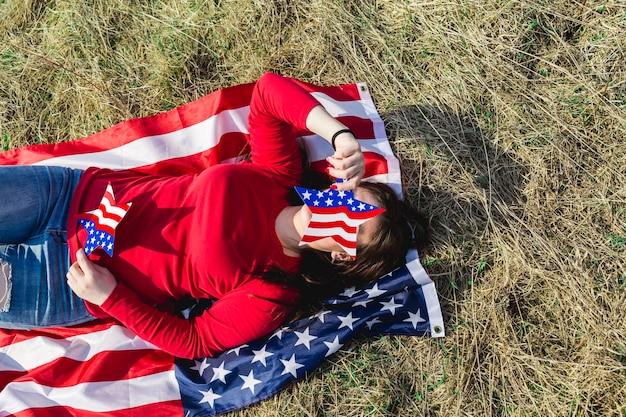 Frau, die auf gewebe der amerikanischen flagge auf feld liegt