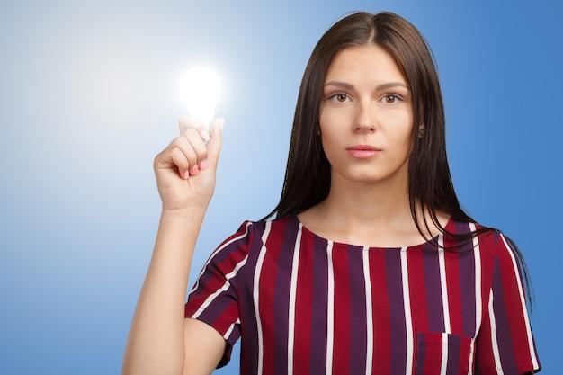 Frau, die auf glühlampe zeigt