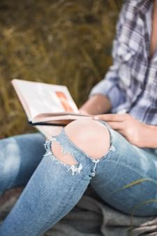Frau, die auf gras mit buch in beunruhigten jeans sitzt