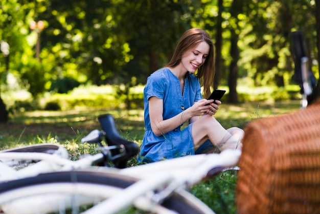 Frau, die auf gras mit defocused fahrrad sitzt