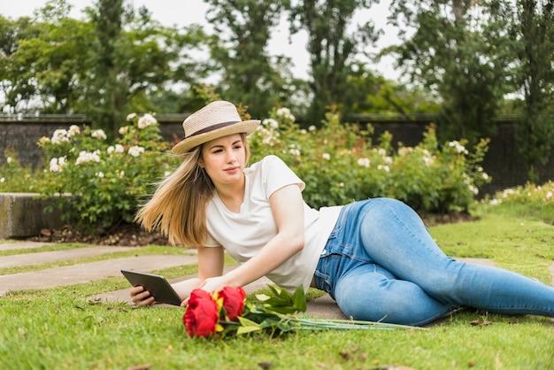 Frau, die auf gras mit tablette liegt