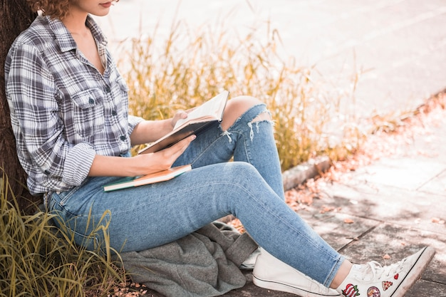 Frau, die auf gras nahe baum und lesebuch sitzt