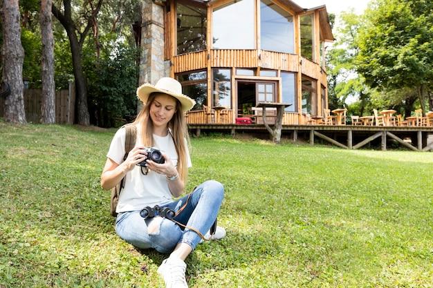 Frau, die auf gras sitzt und ihre kamera betrachtet