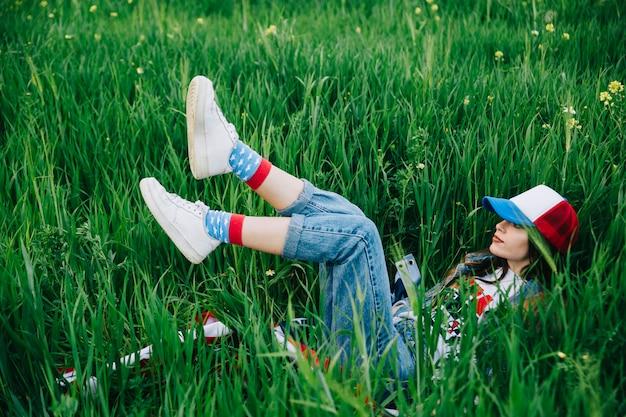 Frau, die auf grünem gras in farbiger kleidung liegt