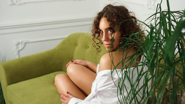 Frau, die auf grünem sofa im wohnzimmer sitzt. schöne lange beine. schöne frau mit lockigem haar in weißen dessous zu hause - glücklicher morgen