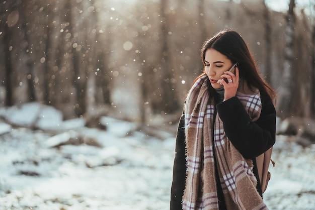 Frau, die auf handy spricht. lächelnde frau, die am kalten wintertag auf handy spricht.
