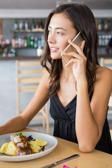 Frau, die auf handy während des essens spricht