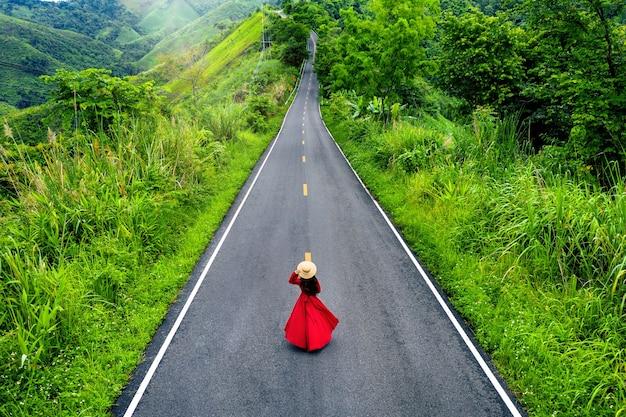 Frau, die auf himmelsstraße über den bergen mit grünem dschungel in der nanoprovinz, thailand geht