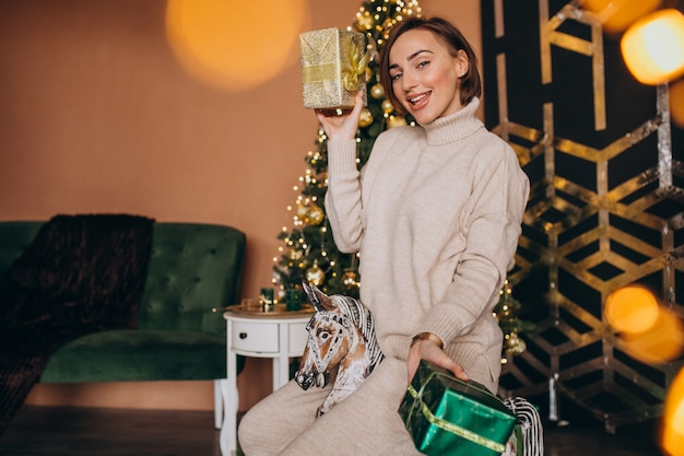 Frau, die auf hölzernem ponystuhl durch den weihnachtsbaum sitzt