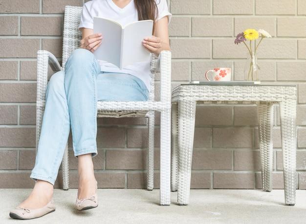 Frau, die auf hölzernem webartstuhl im haus für das ablesen eines weißbuches sitzt