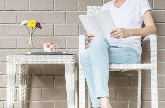 Frau, die auf hölzernem webartstuhl im haus für das lesen eines weißen buches in der freizeit am nachmittag sitzt