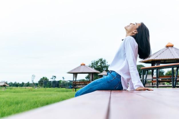Frau, die auf hölzerner brücke mit ihren beinen unten hängen sitzt und sich entspannt