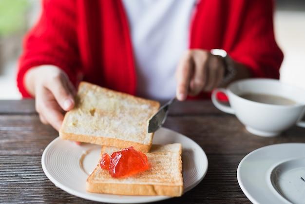 Frau, die auf hölzerner tabelle frühstückt