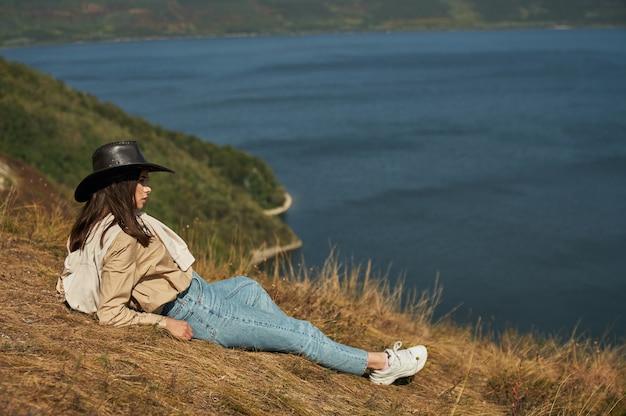Frau, die auf hohem hügel liegt und landschaftlich reizvolle landschaft genießt
