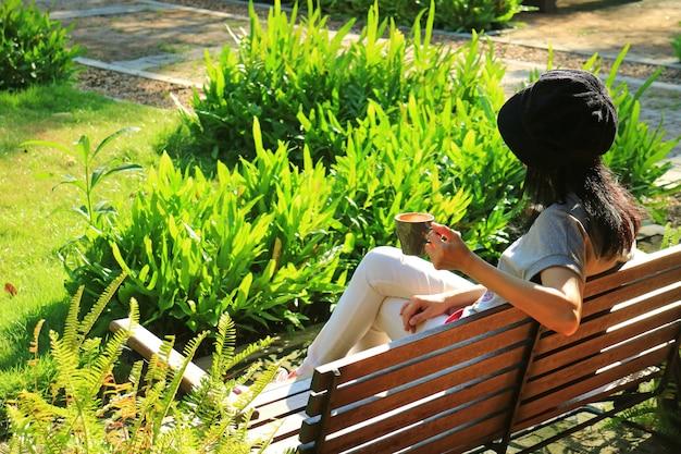 Frau, die auf holzbank im vibrierenden grünen garten hält eine schale heißen kaffee sich entspannt