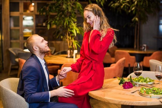Frau, die auf holztisch sitzt und hand des mannes hält