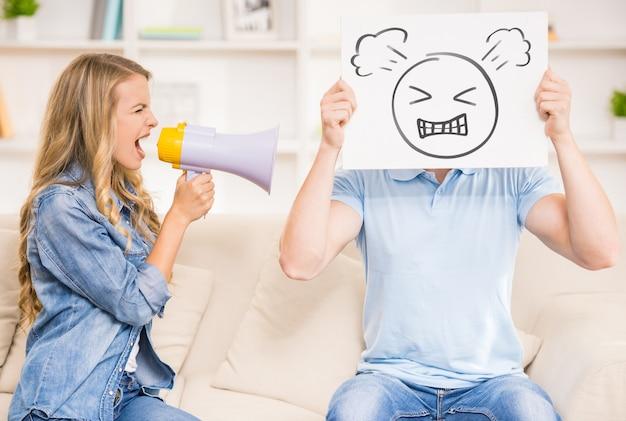 Frau, die auf ihrem ehemann mit mundstück schreit.
