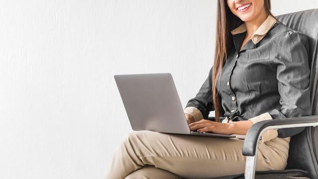 Frau, die auf ihrem stuhl bei der arbeit mit kopienraum sitzt