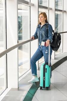 Frau, die auf ihren flug mit koffer wartet