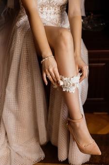 Frau, die auf ihren sexy brautstrumpfbandwurf des beines, im zarten beige kleid sich setzt