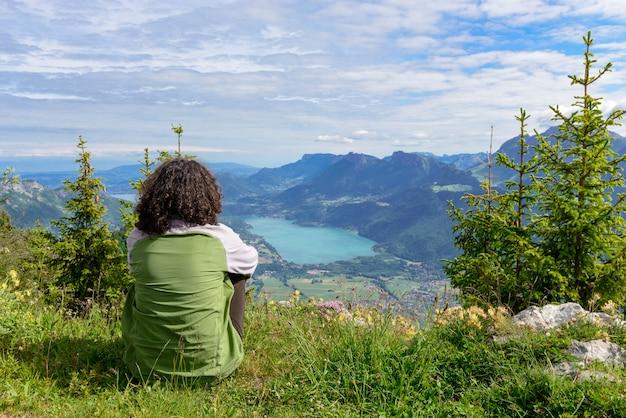 Frau, die auf klippe sitzt und landschaft betrachtet
