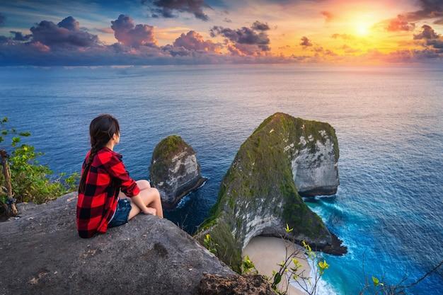 Frau, die auf klippe sitzt und sonnenuntergang am kelingking-strand in nusa penida insel, bali, indonesien betrachtet.